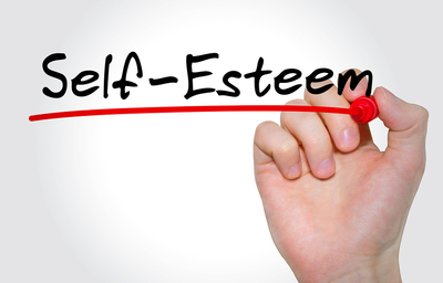 Person writing the word self-esteem in black with a red link underneath.