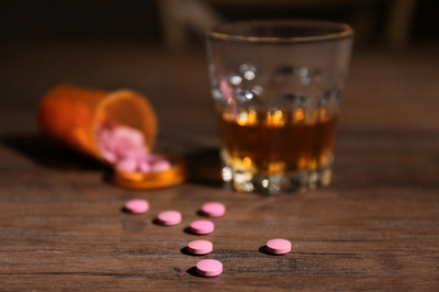 Bottle with pink pills spilling out of it next to a glass with amber colored alcohol.