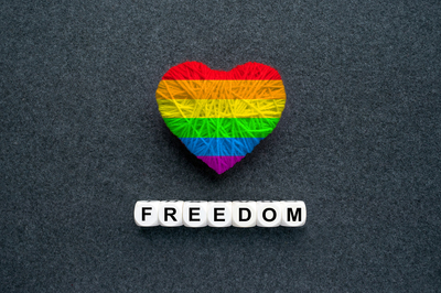 Rainbow colored hart and the words freedom below it.