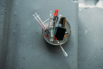 Syringes and rolled dollar bills in a glass ashtray.