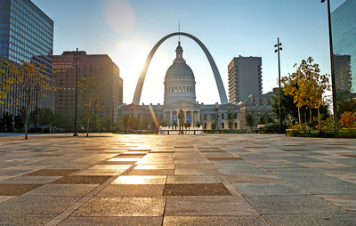 Photo of the arch in St. Louis with buildings around it.