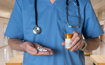 Medical doctor holding a pill bottle.