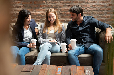 Three people sitting on a couch drinking coffee.