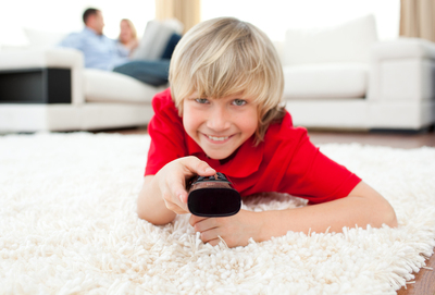 Young boy using a tv remote.