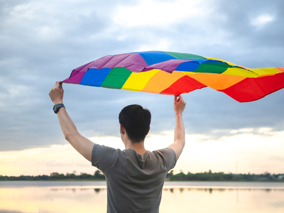 Man holding a rainbow flag over his head.
