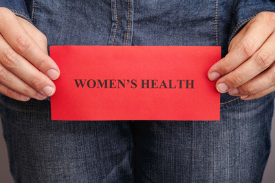 Person holding a sign labeled Women's health.