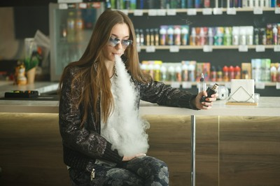 Woman sitting at a bar and vaping.