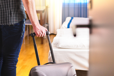 Person moving into a drug rehab with a suitcase.