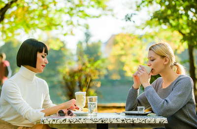 Two women sitting at a dinner table drinking coffee.