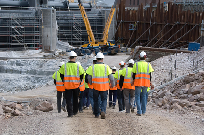 Group of workers with reflective vests and hard hat entering a construction site.