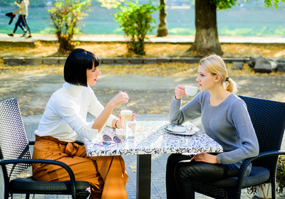 Two women sitting at a cafe outside drinking coffee.