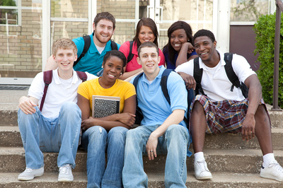 Group of young adults sitting on steps with backpacks.