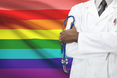 Medical doctor standing in front of a rainbow flag.