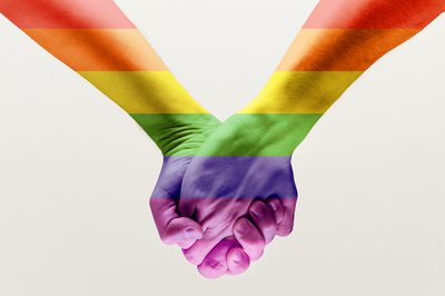 Two people holding hands that are rainbow colored.