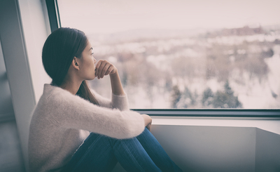 Woman sitting and looking out a window.
