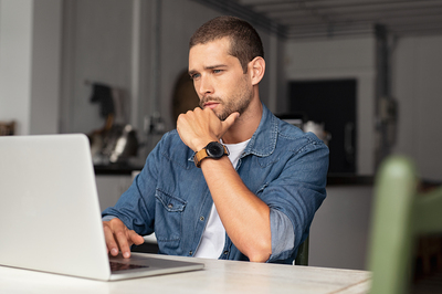 Man looking intently at his laptop screen.