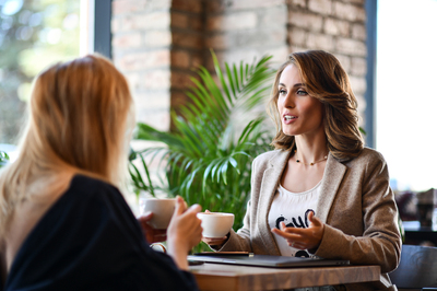 Two women having a conversation in a cafe.