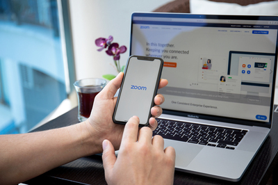 Zoom app displayed on a phone and laptop.