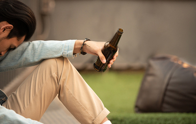 Man sitting alone drinking a beer.