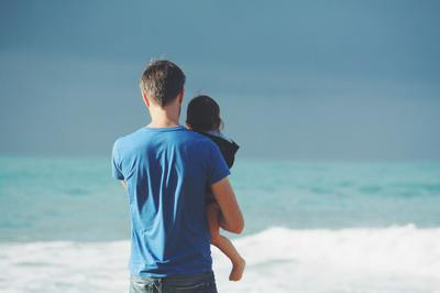 Father carrying a child on the beach.