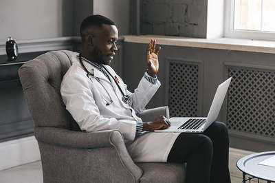 Medical doctor sitting in a chair using his laptop for a Telehealth visit.