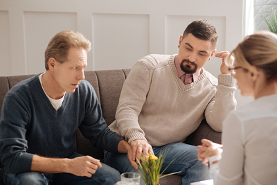 Gay couple meeting with a therapist.