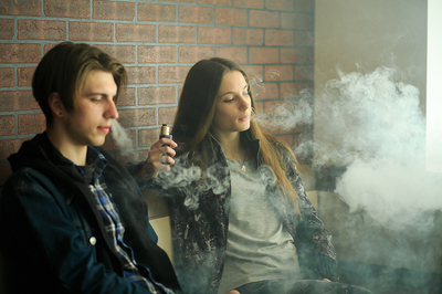 Two teens vaping.