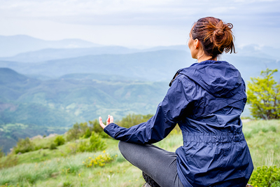 Woman sitting outside in a yoga pose.
