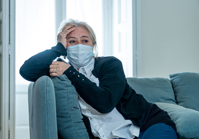 Woman sitting on her couch wearing a protective face mask.