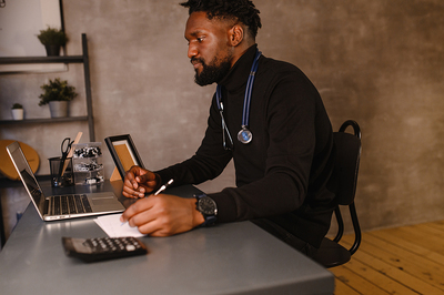 Medical doctor using a laptop for a telemedicine visit.