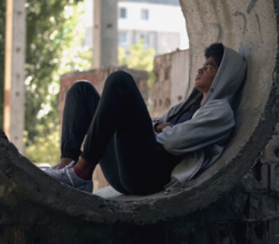 Teen sitting outside appearing sad